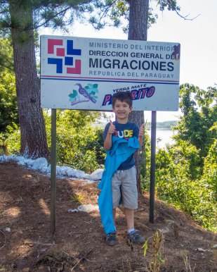 A young boy poses in front of the immigration sigh at the Argentinian and Paraguayan border