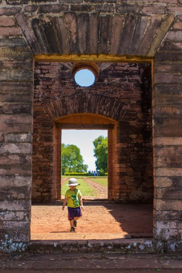 A young boy strolls through doorways in the ruins of Jesuit missions in Paraguay