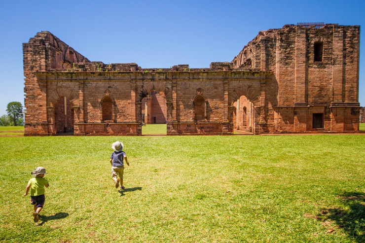 Two young boys running towards the ruins of a Jesuit Mission in Paraguay