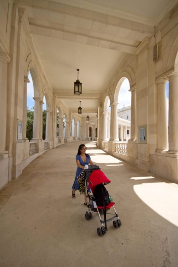 a woman pushes a stroller through the bright arched walkways of the shrine of Fatima in Portugal