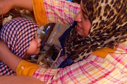 A Bedouin shopkeeper help D put on a headscarf in Petra Jordan