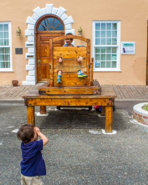 Boy playing in a pillory in the town square of St George Bermuda.