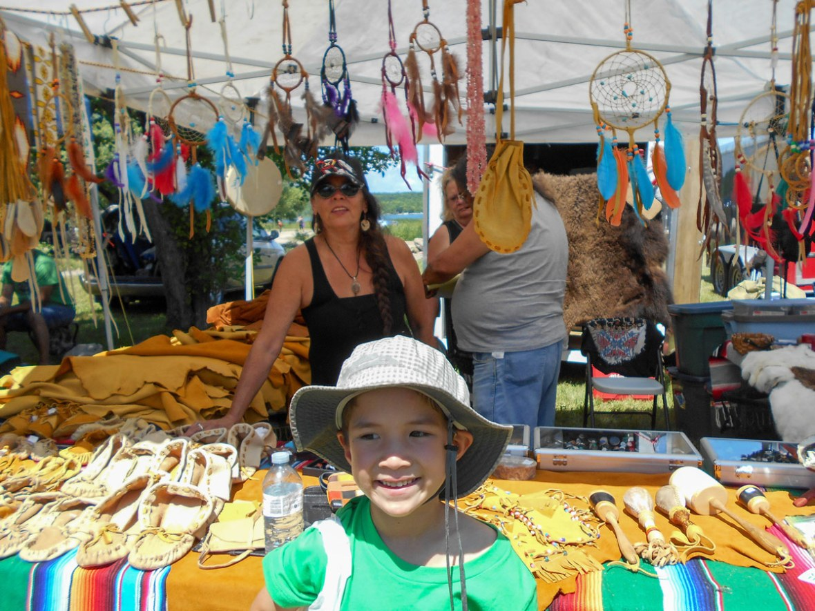 A young boy smiles next to experience a first nations pow wow in Ontario