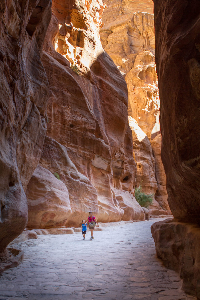 Christina and C are dwarfed by the towering walls of al siq , one of the first examples of what to see in Petra with kids
