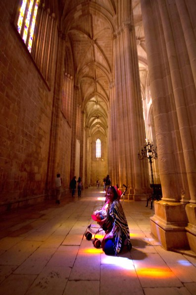 Mother and son pose in the colorful reflection of the stained glass windows inside the Batalha Monastery.