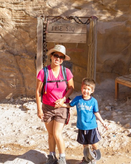 A mother and son pose by the sign for the siq as they explore what to see in Petra with kids