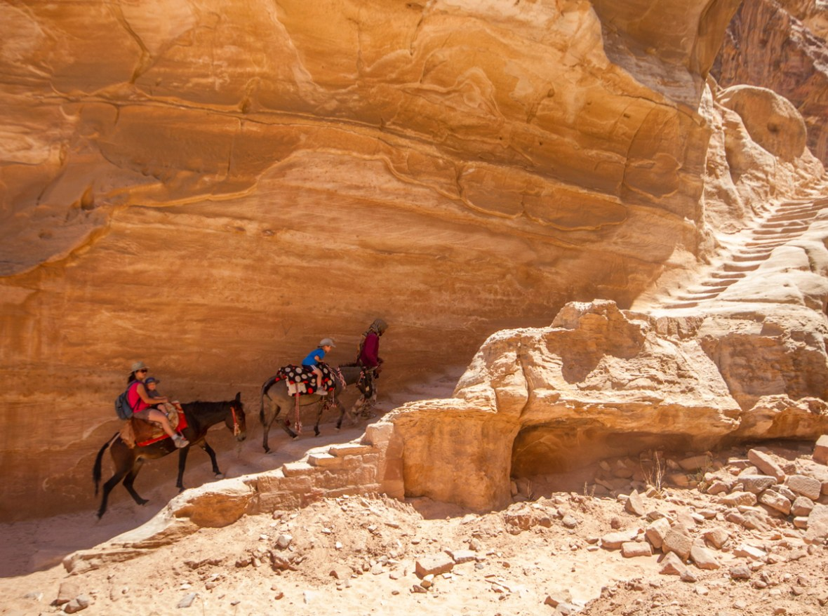 A Bedouin guides a woman and two young boys on horseback up stairs in Petra Jordan