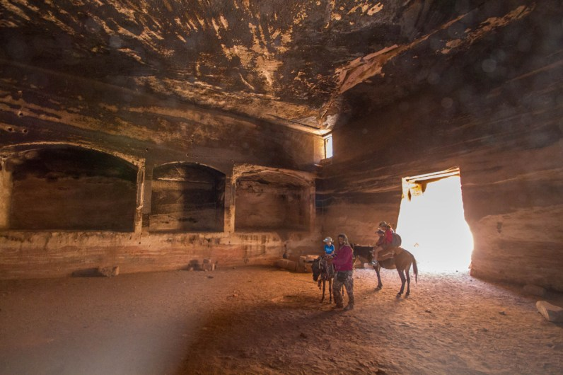 A Bedouin guides a woman and two boys on horseback through the tomb of the roman soldier in Petra Jordan