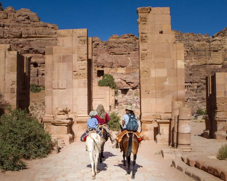 A Bedouin guides a mother and two young boys on horseback through the Tremenos Gateway in on the way to the Monastery