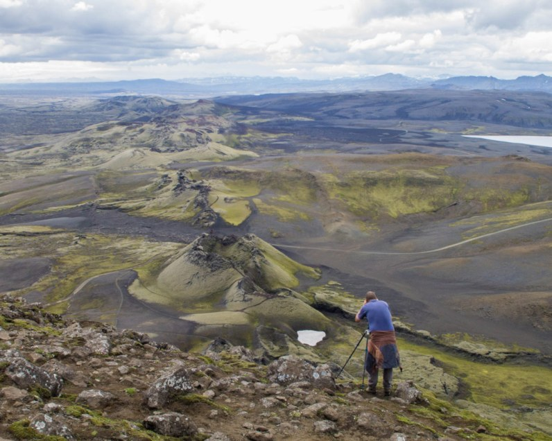A photographer takes photos of a row if volcanic craters in Laki Iceland