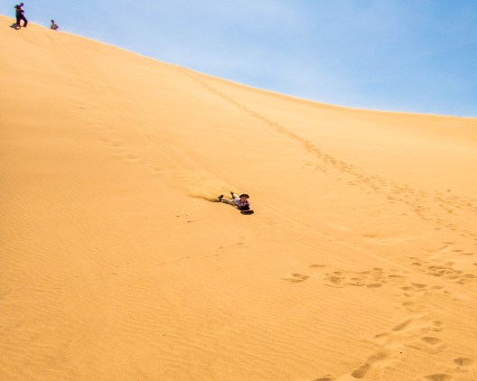 A young boy races down a sand dune on a sandboard in Peru