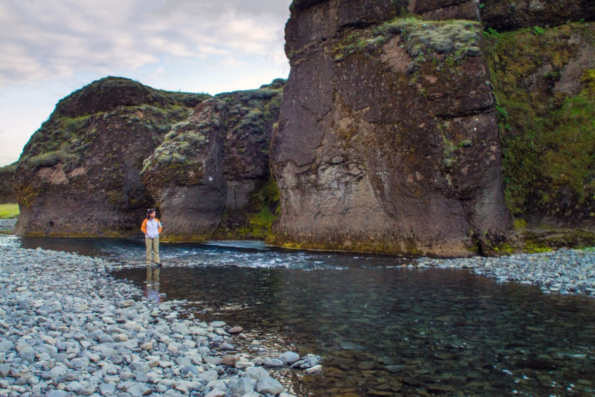 A woman wades through a river in Fjadrargljufur canyon in Iceland