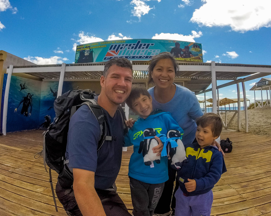 A mixed race family takes a selfie outside of a dive shop in Puerto Madryn Argentina