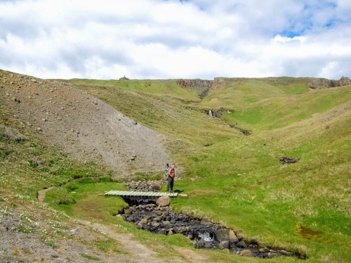 A man carrying a child on his back crosses a bring while hiking up to Hengifoss in Iceland