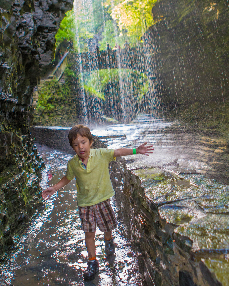 Boy playing under a waterfall at Wakings Glen State Park.