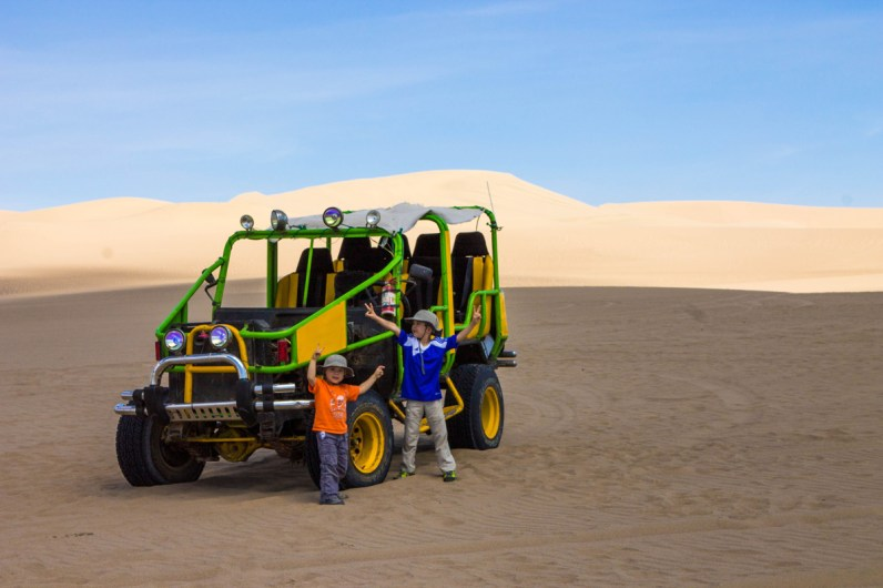 Two young boys stand next to a massive dune buggy as they go Sandboarding in Huacachina Peru