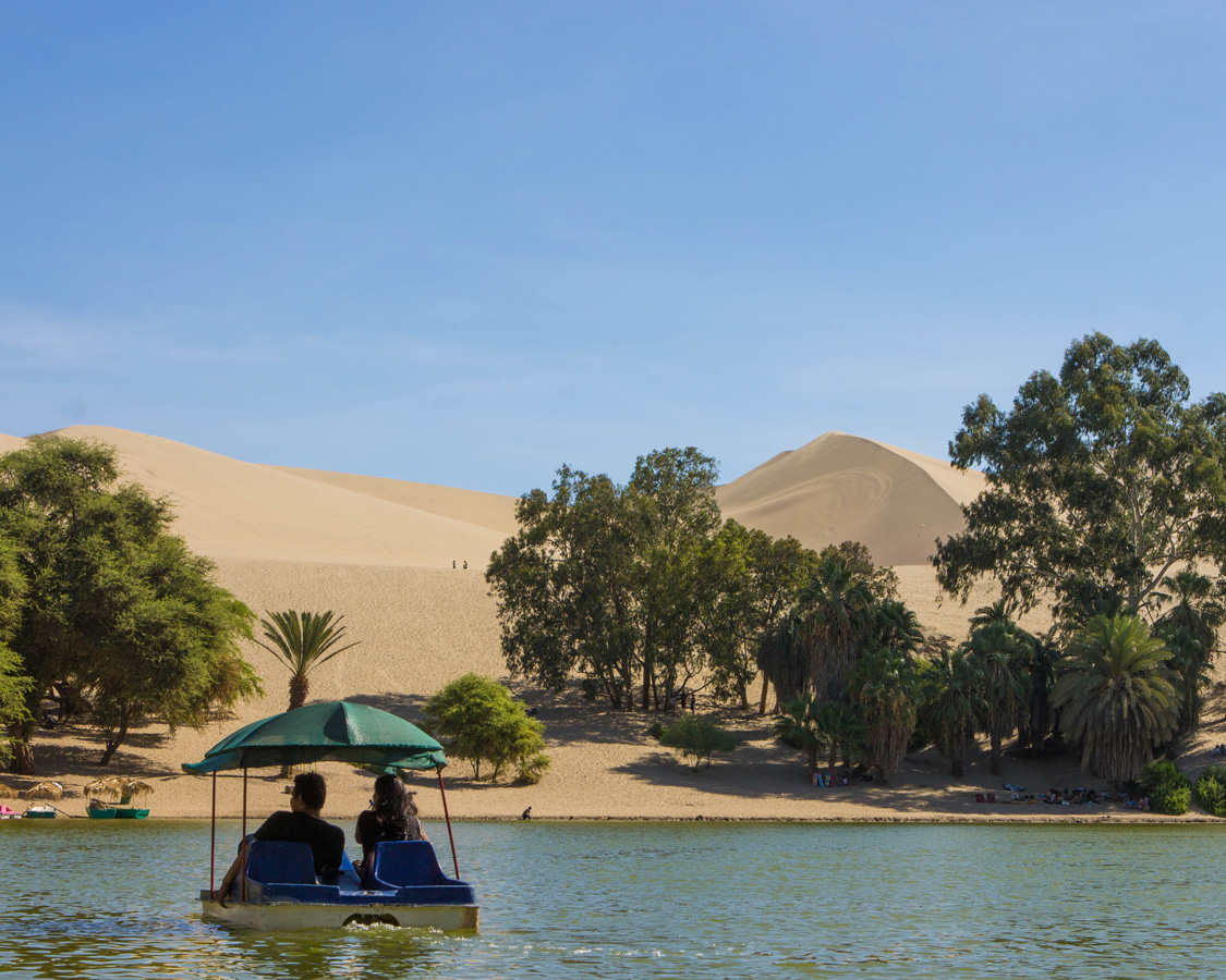 Boaters explore the oasis in Huacachina Peru, a perfect place to relax while sandboarding with kids in Peru
