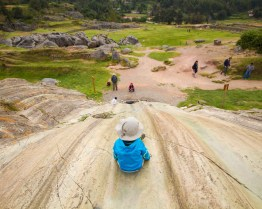 A young boy gets ready to slide down a rock slide in Sacsayhuaman before going to the chocomuseo in Cusco Peru
