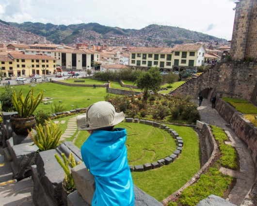 A young boy looks out onto the garden of Santo Domingo and Coricancha before visiting teh Choco Museo in Cusco Peru