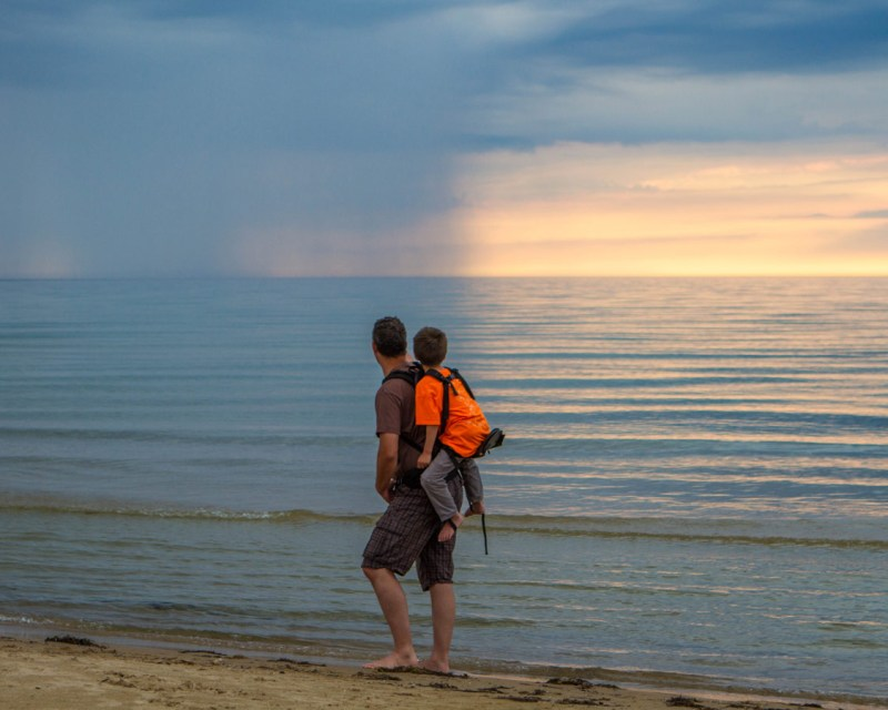 A father carries a child along a beach. The child sitting high on the Freeloader Child Carrier as they pass by a sunset and rain clouds