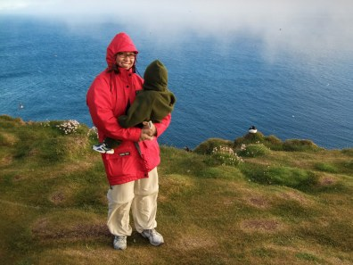 A woman wearing a red rain jacket faces the camera while a toddler in a green fleece suit faces away looking at birds at the top of a tall cliff