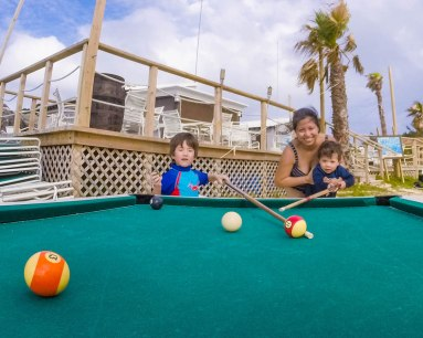 A young family plays pool at the Tobacco Bay cafe in Bermuda with kids