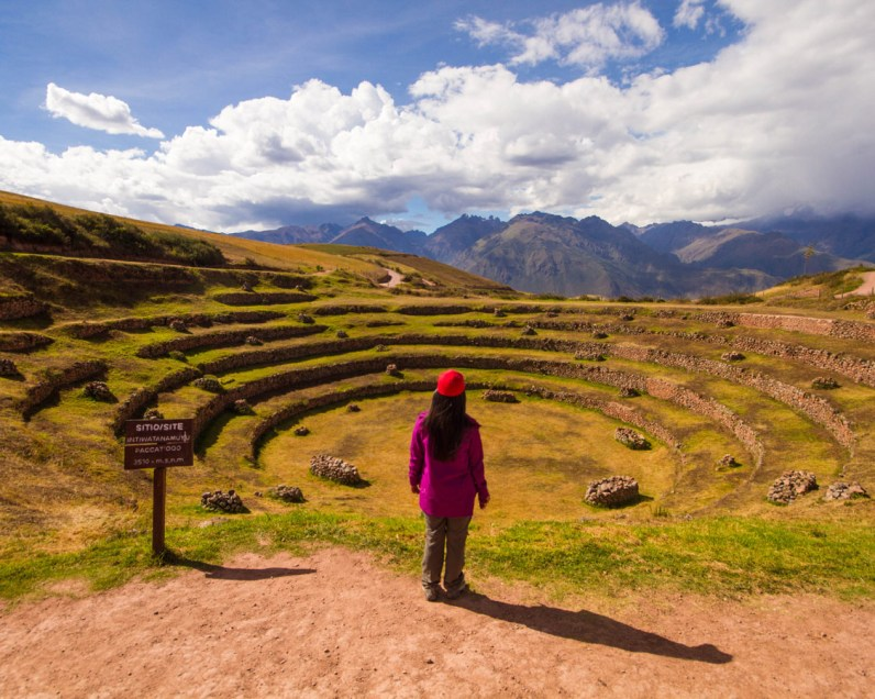 A woman in a purple jacket and red hat looks out over the green Incan terraces of Moray Peru