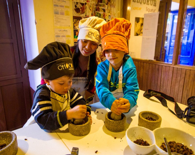 Two young boys wearing colorful chef hats grind chocolate beans at the ChocoMuseo in Cusco Peru while their mother looks on smiling