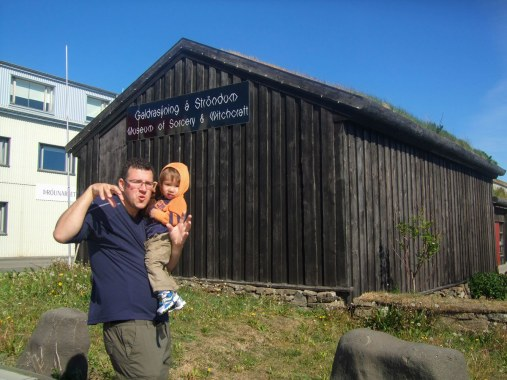 A man makes a funny face while holding a toddler in front of the witchcraft and sorcery museum in Holmavik, Iceland