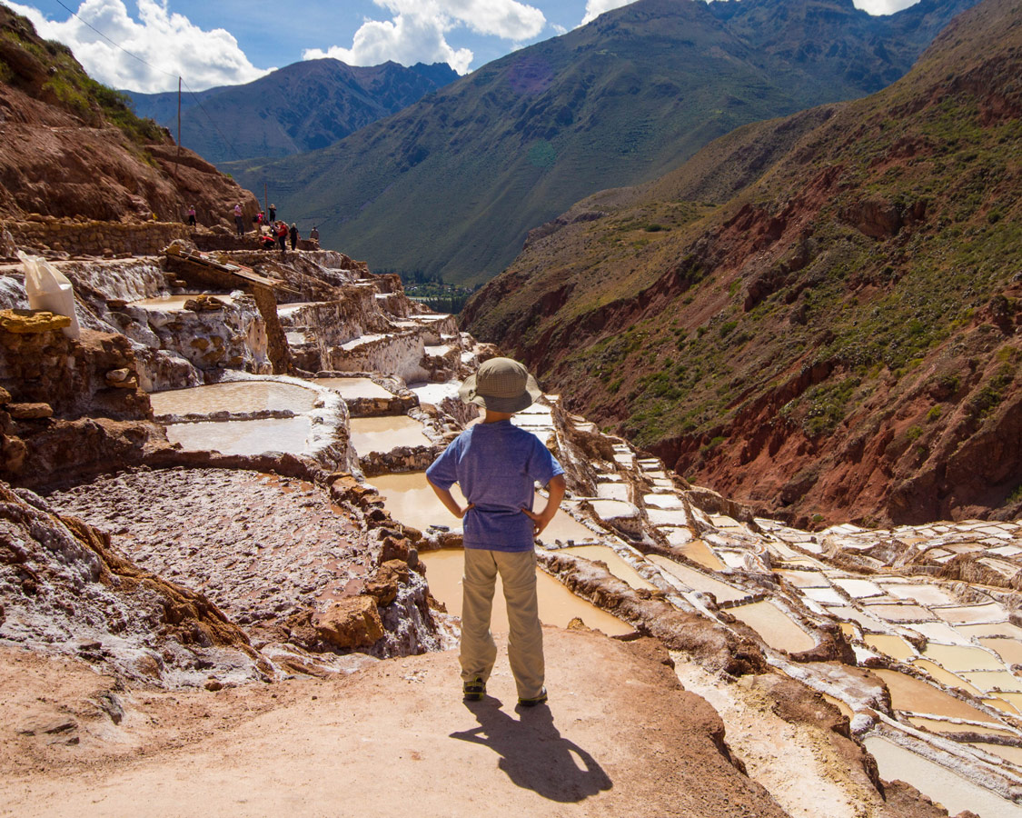 A young boy with his hands on his hips looks out over the salt pans of Maras Peru while Visiting Maras and Moray with kids