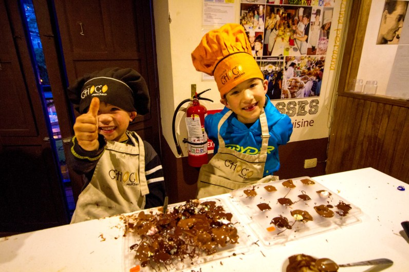 Two young boys wearing colorful chef hats give thumbs up over one very clean and one very messy chocolate molds at the ChocoMuseo in Cusco Peru