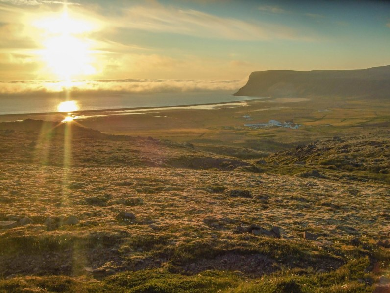 Sunset view of the grasslands and coast of Iceland's westfjords. in the middle is a small hotel with campgrounds
