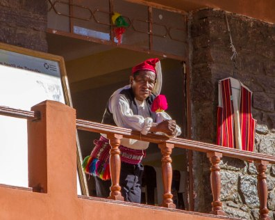 A Taquileano man wearing a black vest and colourful hat and belt stands outside a garment shop on Isla Taquile on Lake Titicaca Peru