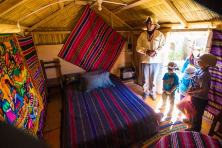 An Uros elder shows off a hotel room on the reed islands of Lake Titicaca Peru while children look on. You can visit this hotel while visiting Lake Titicaca with kids