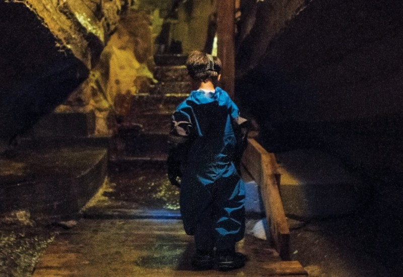 A young boy in a blue caving outfit walks through Bonnechere Caves with kids in Eganville, Ontario