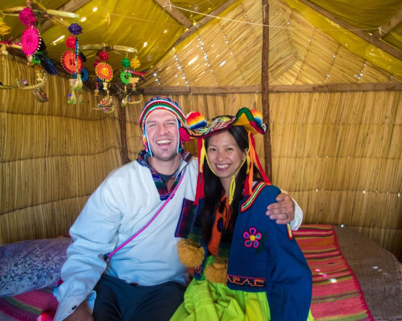 A man and woman smile while wearing traditional Uru clothing while visiting Isla de los Uros on Lake Titicaca with kids