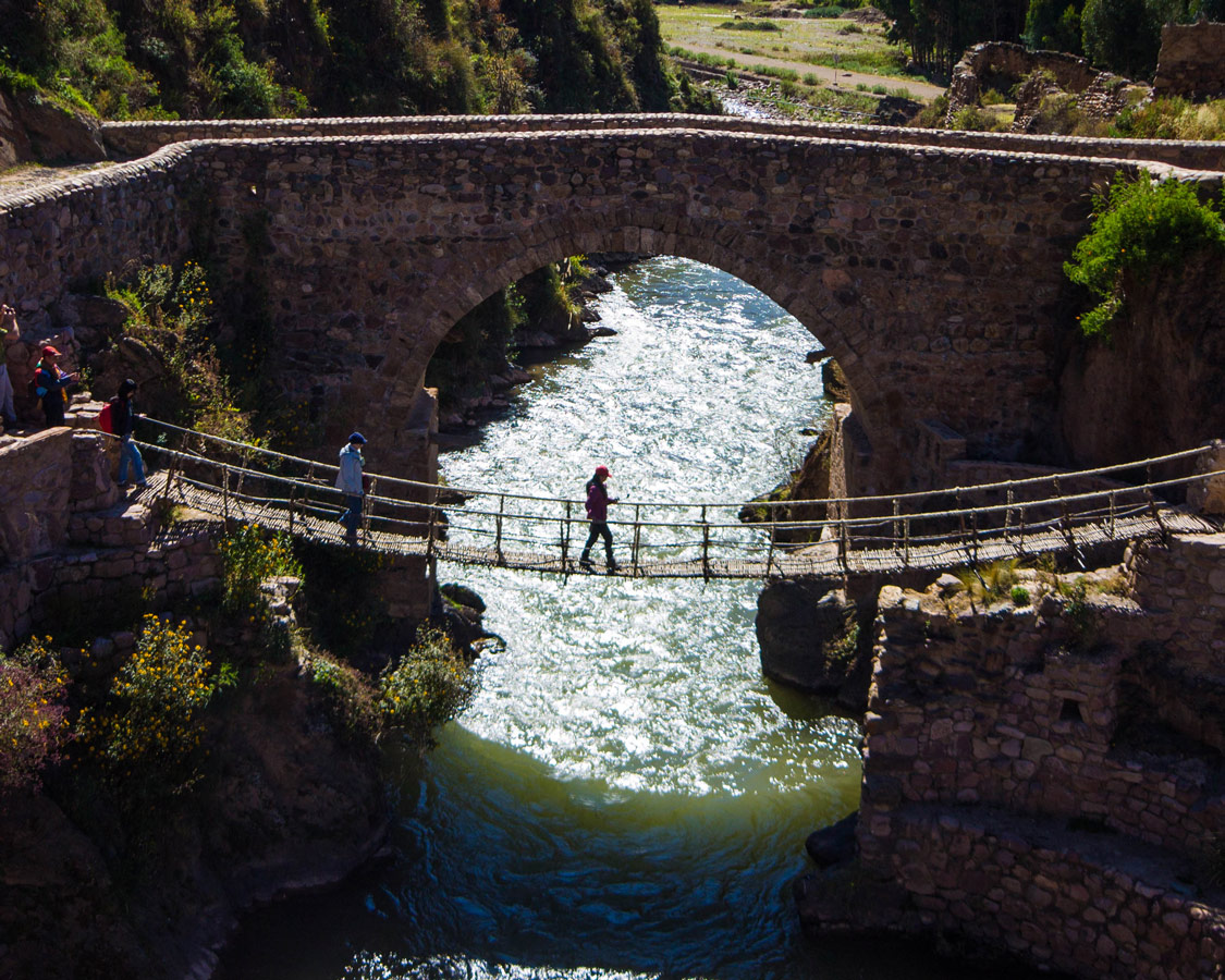 The Cusco to Puno bus stops in Che Cupa where a woman crosses the last Inca rope bridge. A colonial bridge spans the river behind it