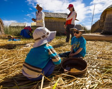 A tourist toddler chats with a local Uru boy on the reed islands of Lake Titicaca as his family visits Lake Titicaca with kids