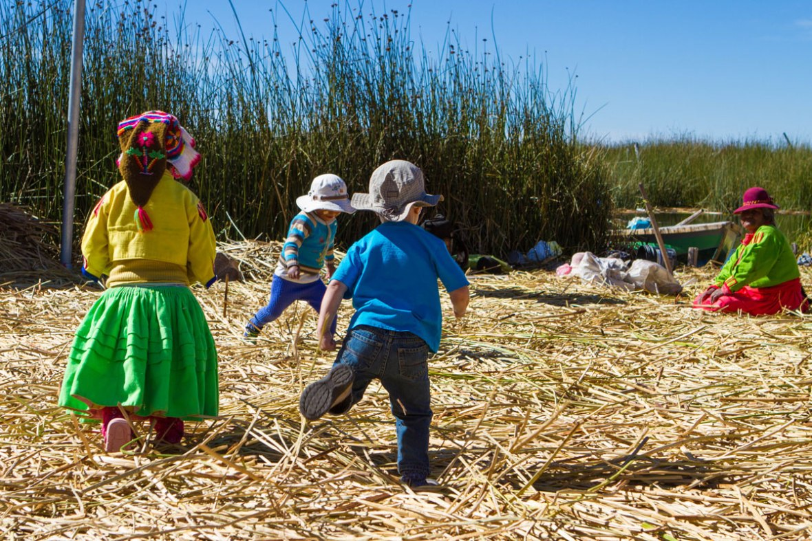 Tourist children play with local Uru children on the reed islands of Lake Titicaca while their family visits Lake Titicaca with kids