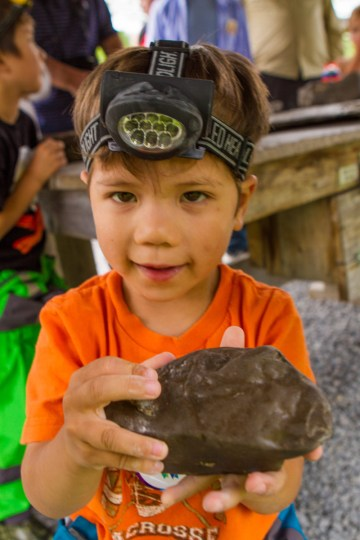 A toddler wearing a caving headlamp shows off a fossil at Bonnechere Caves with kids