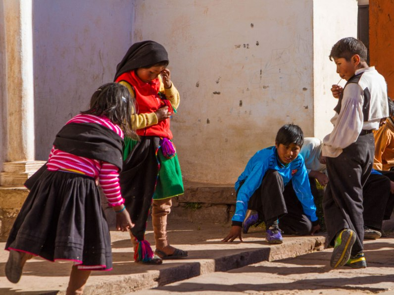 Taqileano children play marbles outside a church on Isla Taquile in Lake Titicaca Peru. Playing marbles with the locals was a fun part about exploring Lake Titicaca with kids