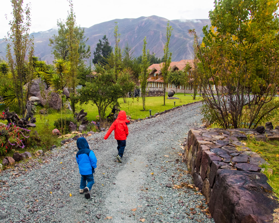 Two young boys wearing colorful rain jackets run along a path at the Casa Andina Private Collection Sacred Valley Peru