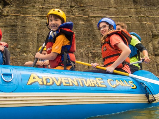 A young boy smiles from inside the Adventure Calls Outfitters Raft in Letchworth State Park in New York State