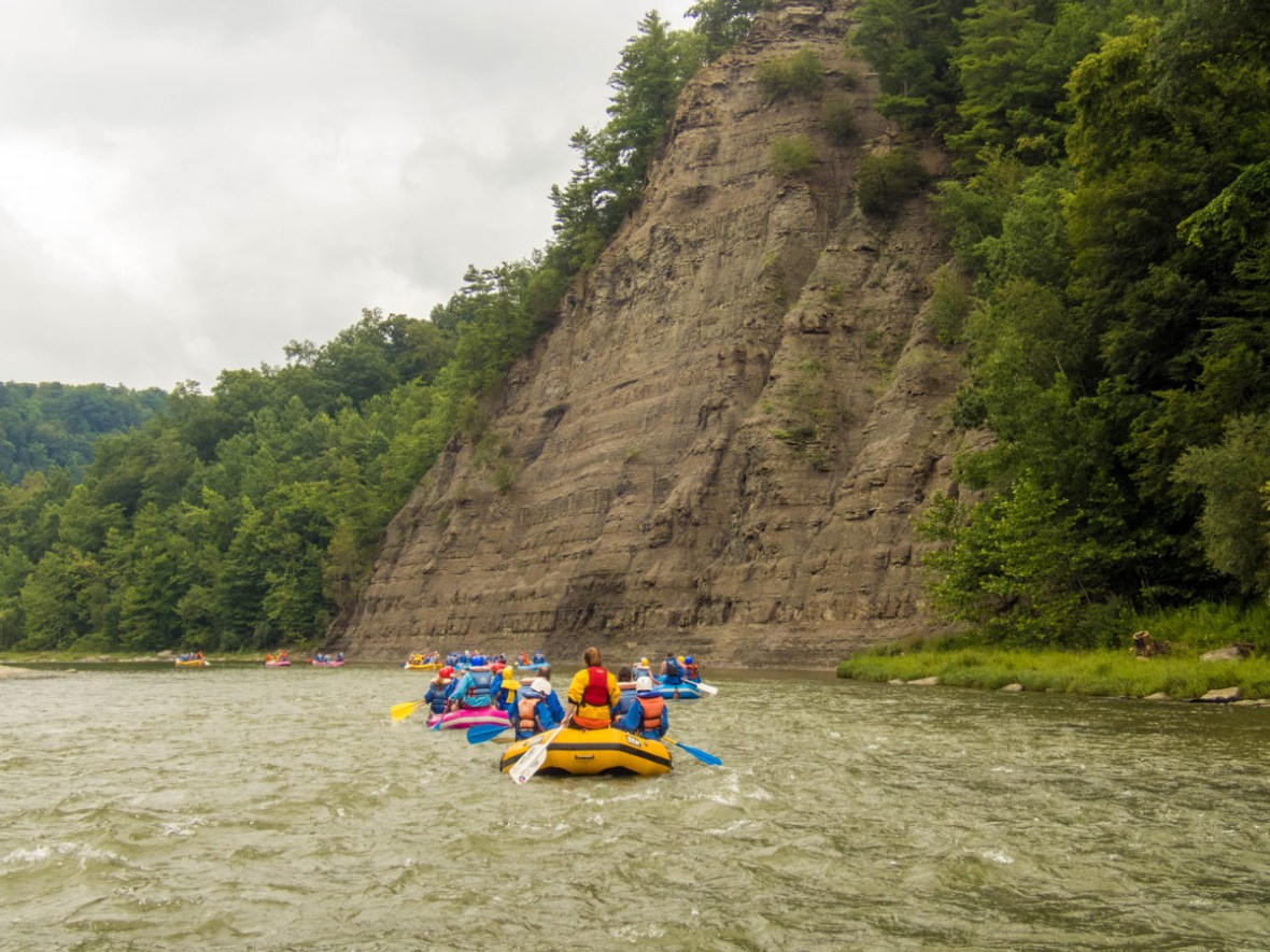 A yellow and a blue raft full of people rafting the river in Letchworth State Park in New York State