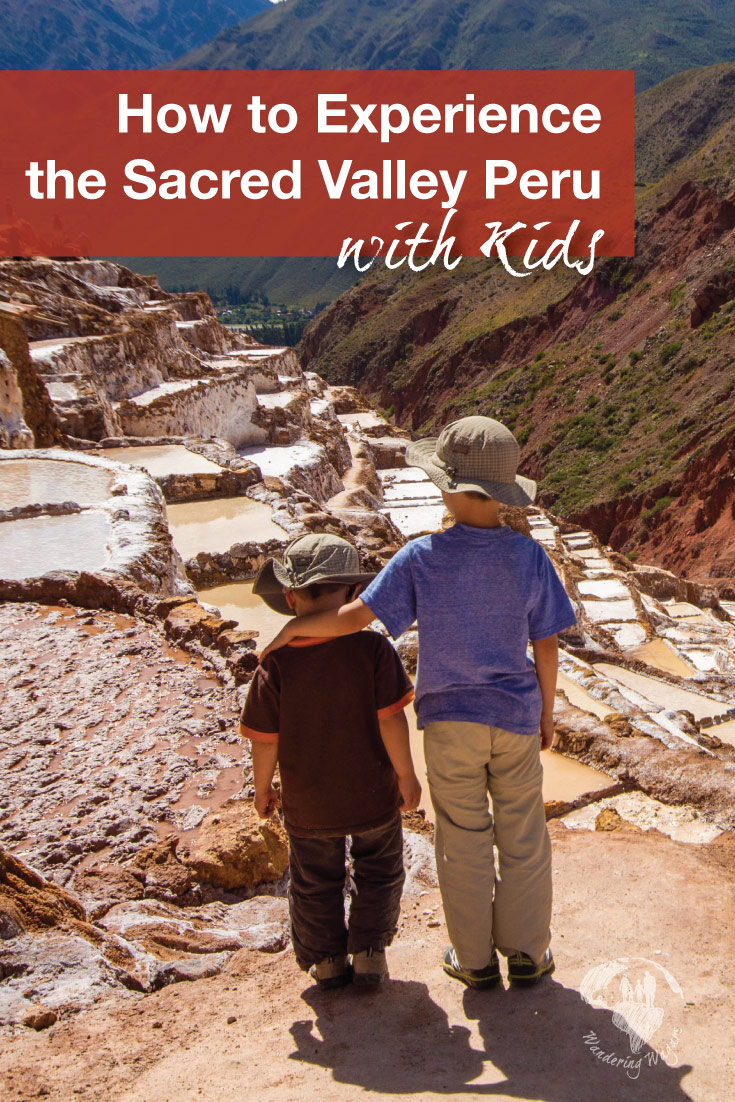 Two young Wandering Wagars boys look out over the salt pans of Maras Peru on a day trip to the Sacred Valley Peru with kids