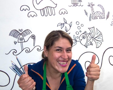 A Peruvian artist smiles and gives two thumbs up in front of a wall of inca style sketches