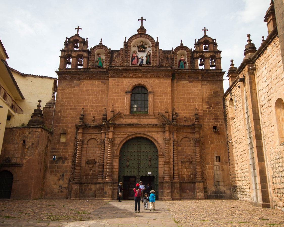 Tourists enter the huge doors of the catholic cathedral in the Plaza d'Armas . It is one of the top things to do in Cusco Peru