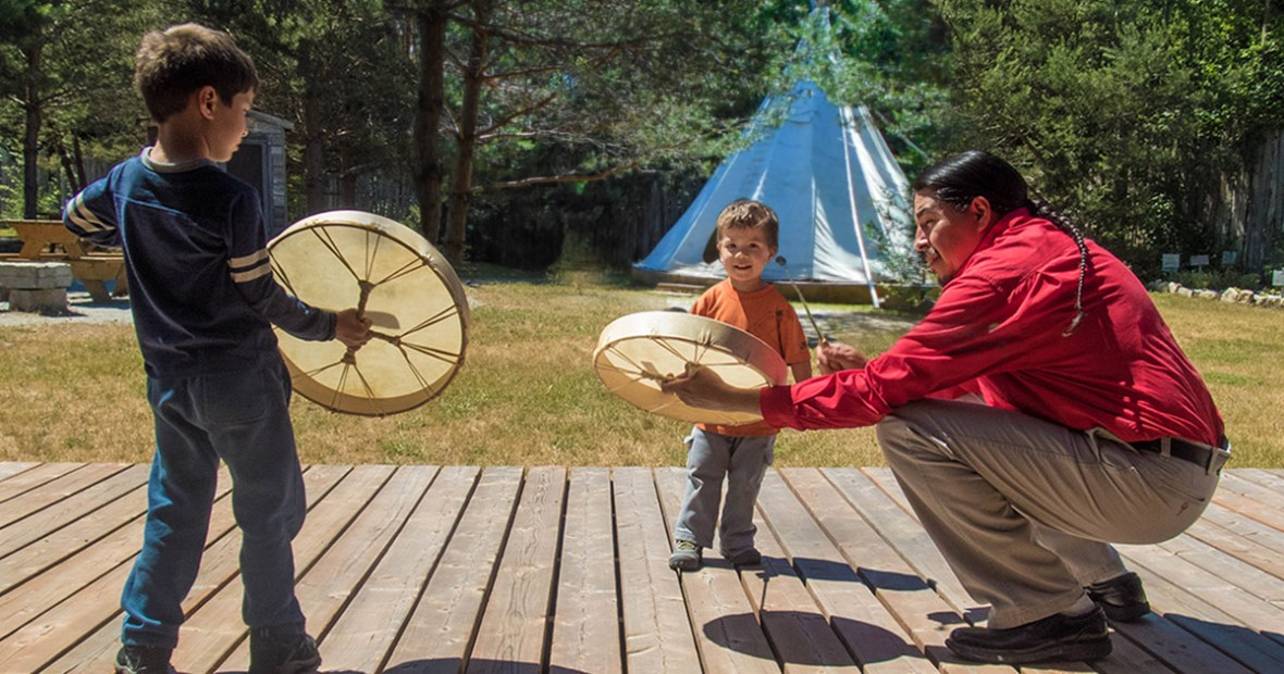 An Ojibwe man teaches two young children about the voice of the drum at the Great Spirit Circle Trail on Manitoulin Island. The Great Spirit Circle Trail is one of the best things to do on Manitoulin Island