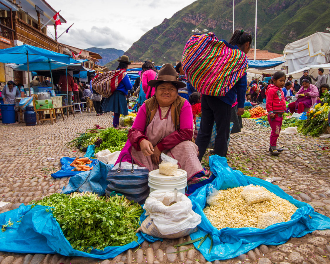 A Quechua woman sells food and grains at the Pisac Market in Peru with kids on a 14 day Peru itinerary