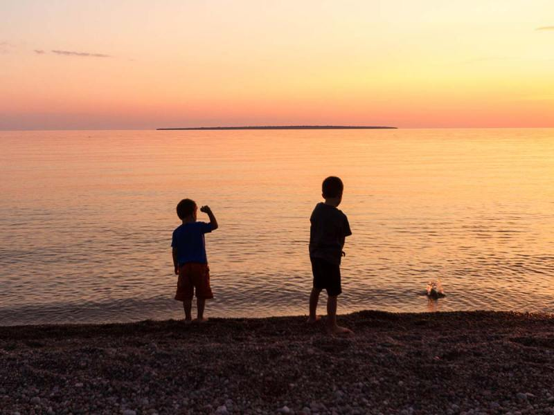 Boys throwing stones in the water at Lake-Superior Provincial Park in Ontario